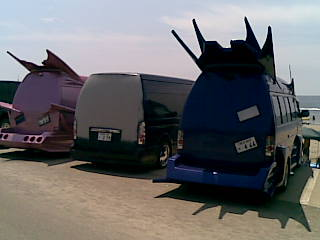 Row of surfer boy vans parked at the beach - one has been temporarily taken out of the workshop for a trip to the beach